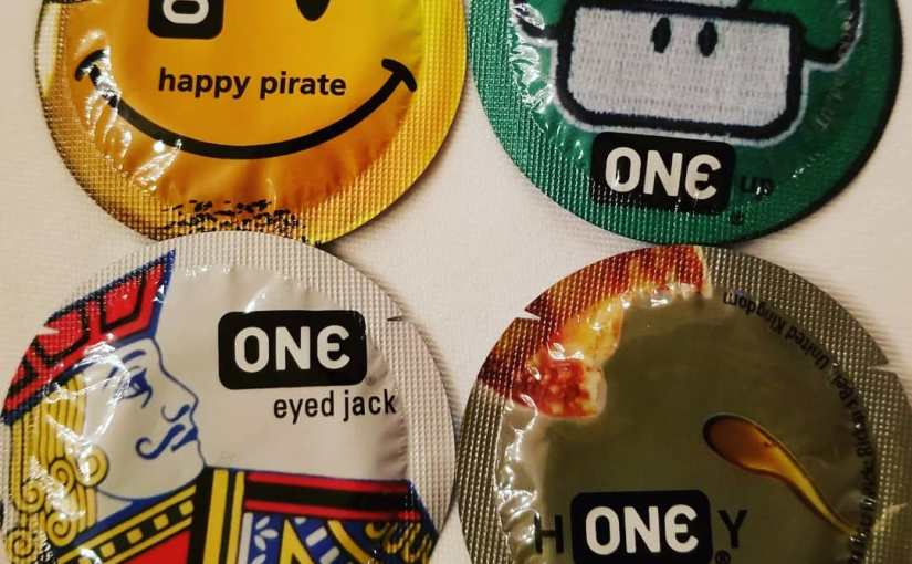 An array of four One brand condoms featuring a smiley face, a mushroom, a one-eyed-Jack, and a honey splotch decorated one