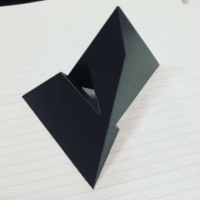 A black plastic Szilassi polyhedron sitting on lined notebook