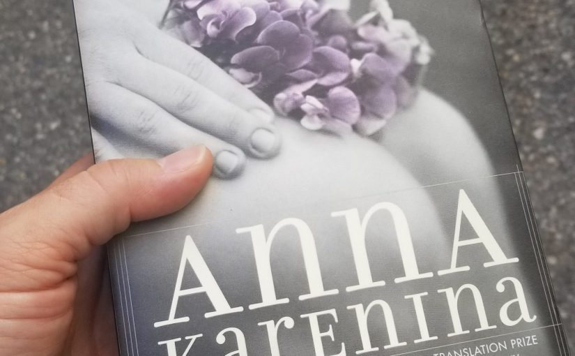 Holding a paperback copy of Anna Karenina by Leo Tolstoy