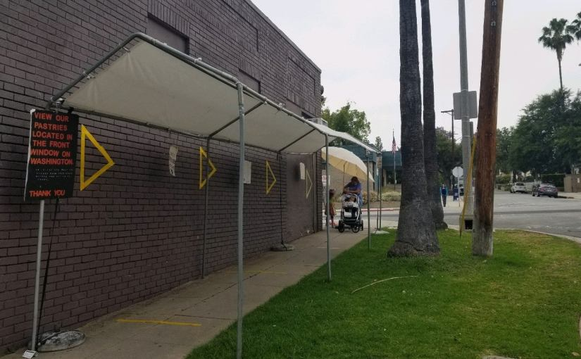 Awning set up next to the bakery to shade the sidewalk for the coronavirus line