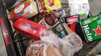 View of my grocery cart full of bread, cheese, raisins, soda, and other miscellanea