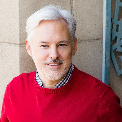 Headshot of Chris Aldrich in a red sweater.