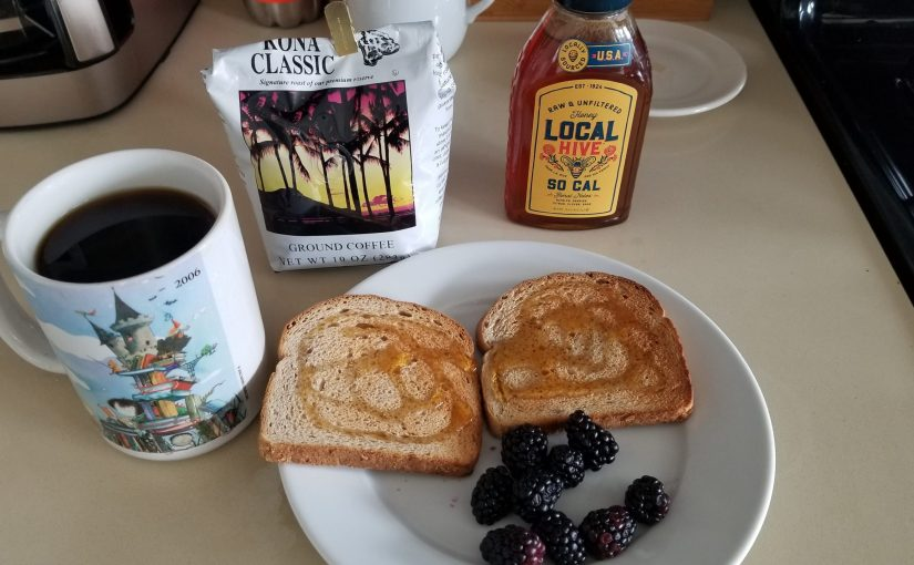 plate of food on a counter with coffee maker, coffee cup, ground coffee in a bag, honey jar nearby