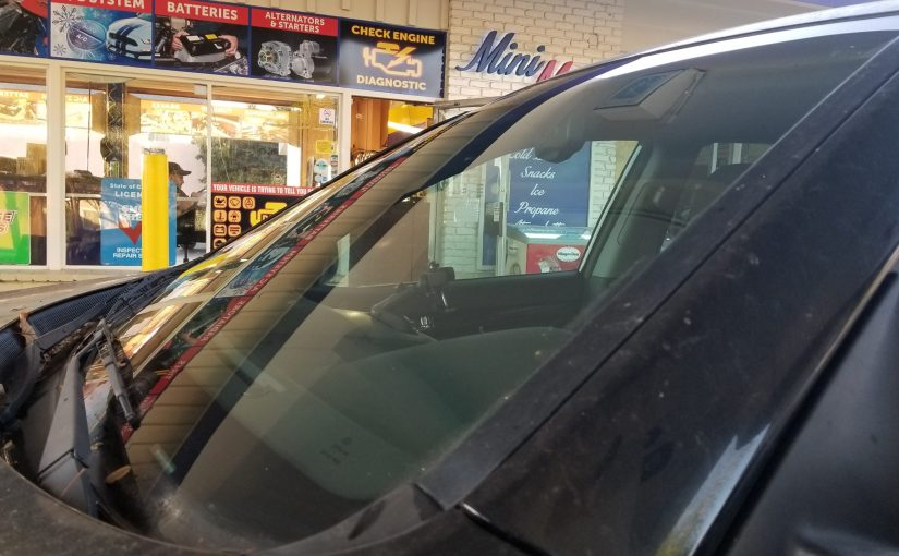 dirty car with clean windshield with gas station in background