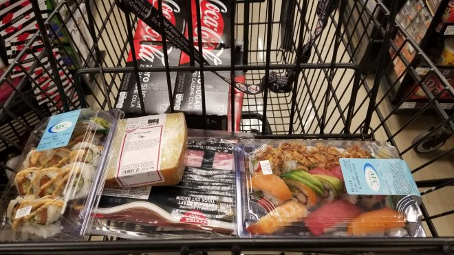 groceries in a shopping basket featuring sushi, soda, cheese, bacom
