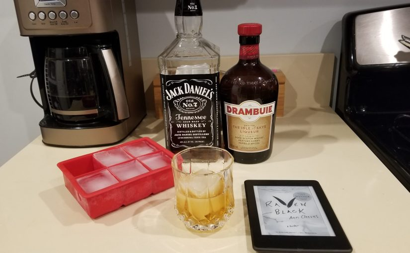 kitchen counter with highball glass of liquor and a large square ice cube, a red rubber ice tray, a bottle of Jack Daniels, a bottle of Drambuie, and a Kindle PaperWhite with the book Raven Black on the screen