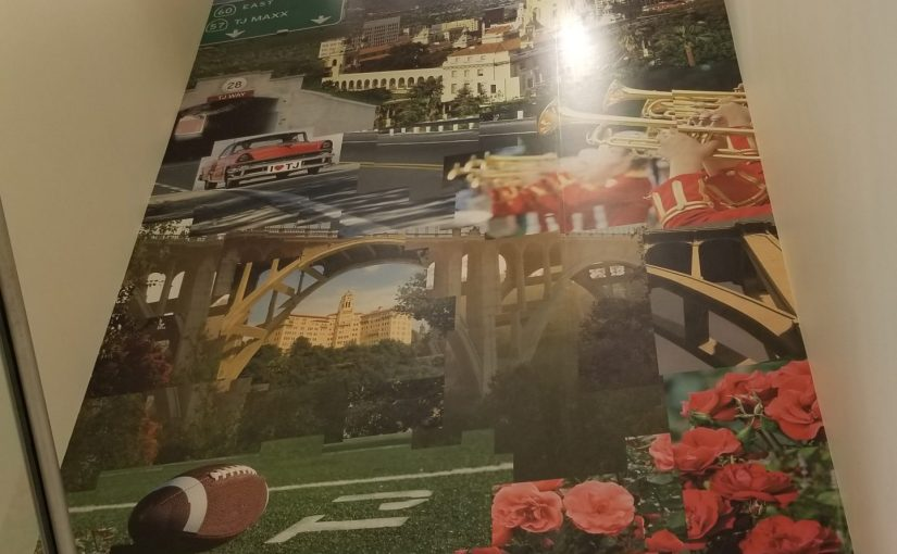 view up at a two story photo mural of Pasadena-related images (Colorado Bridge, roses, etc.) at TJ Maxx