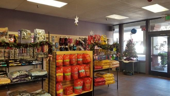 view of product shelves in Dog Zone with a small Christmas tree in the front and a few decorations hanging from the ceiling