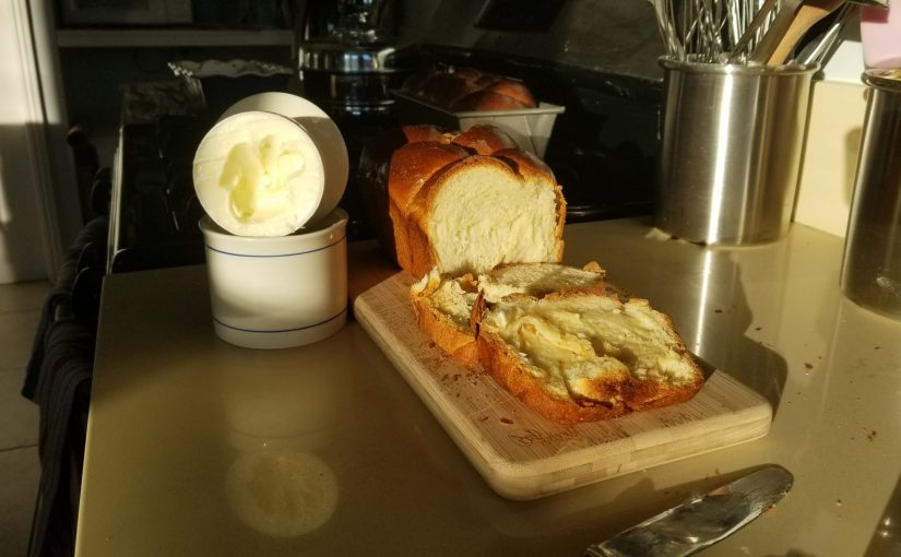 dimming light shows cutting board with fresh loaf of plaited challah next to a butter crock