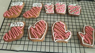 decorated gingerbread cookies cooling on a rack in the kitchen