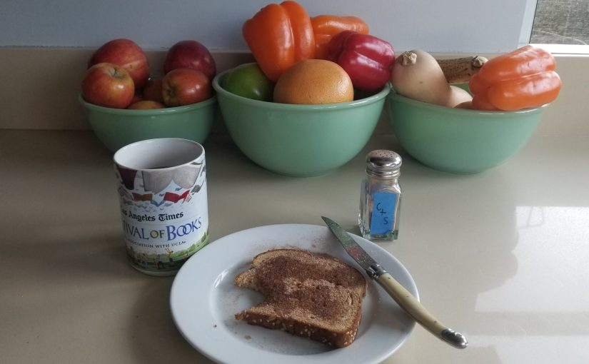 plate with cinnamon and sugar toast with coffee mug, cinnamon & sugar shaker, and bowls of fruit in the background