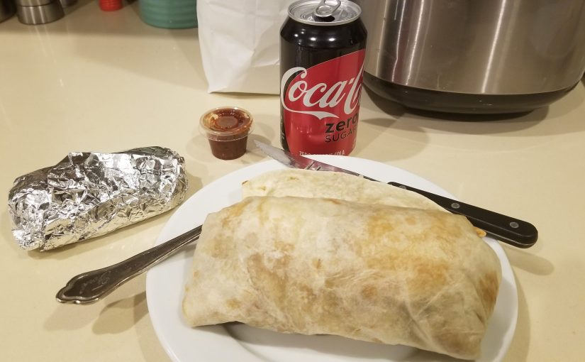 kitchen counter with a burrito and foil wrapped taco on a plate with a can of soda in the background