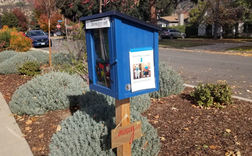"medium shot of our blue Little Free library with a brown sign on the bottom that says ""Merry"""