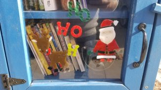 close up of the library door with some Christmas themed gel clings including a Santa and a reindeer
