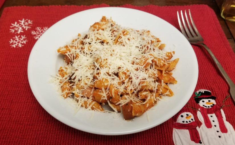 red placemat with snowman design and a plate of pasta
