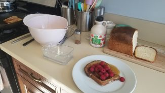 kitchen counter with pink bowl, butter dish, plate with French Toast, syrup, and raspberries. Loaf of bread and syrup in the background