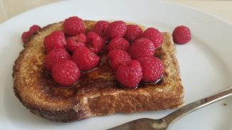 close up of a slice of challah French toast with syrup and raspberries