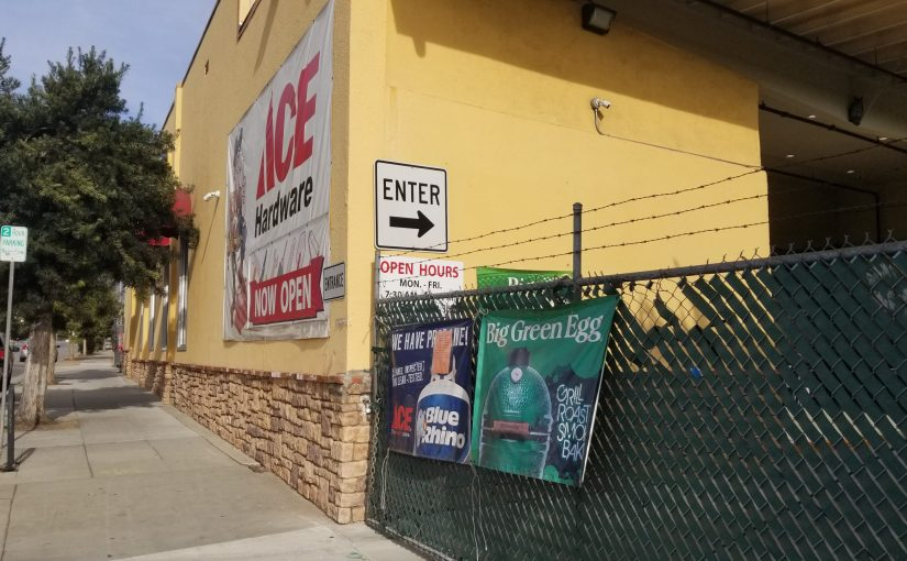 angle on yellow building with ACE Hardware sign and a closed chainlink fence with barbed wire on top