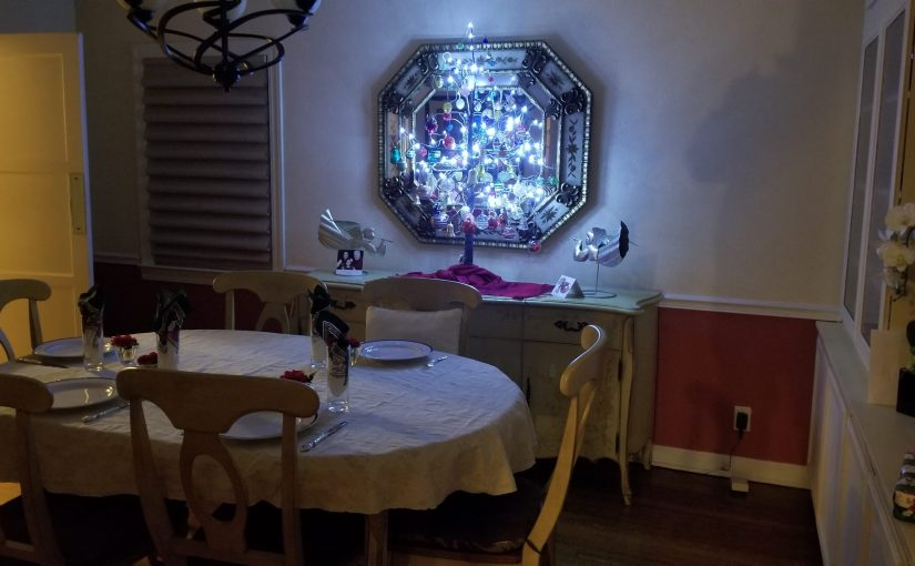 Dining room set for a nice Christmas Eve dinner and a small decorative tree lit up on the sideboard