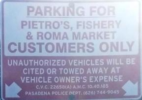 close up of parking sign that reads Parking for Pietro's, Fishery & Roma Market Customers Only. Unauthorized vehicles will be cited or towed away at vehicle owner's expense