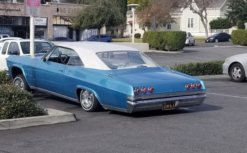 Angle on driver's side of Blue 1965 Impala in a parking lot. The rear is almost on the ground and the front appears hydralulically lifted up higher than a typical car