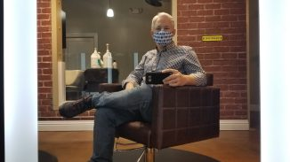 selfie of Chris Aldrich sitting in a salon chair with legs crossed, sporting a new hair cut, and a plaid blue mask