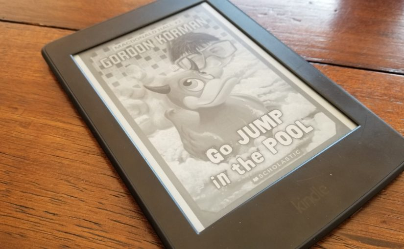 Angle on a Kindle Paperwhite on a wooden dining room table. Kindle features the book cover of Gordon Korman's Go Jump in the Pool featuring a bathtub scene dominated by a child reaching for a rubber duck with devil's horns surrounded by suds