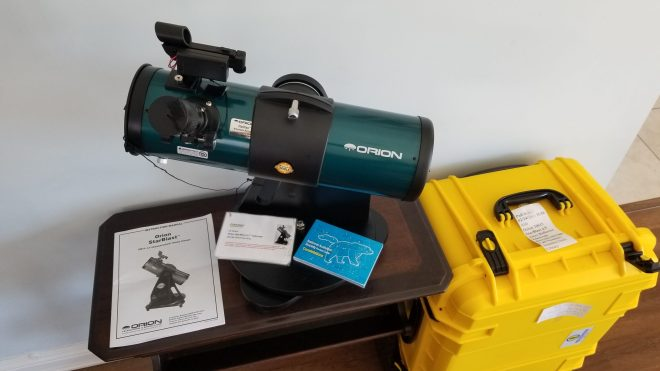 "Orion Starblast 4.5"" Altazimuth Reflector Tabletop Telescope on a small table with instruction manual next to large yellow hard carryingcase"