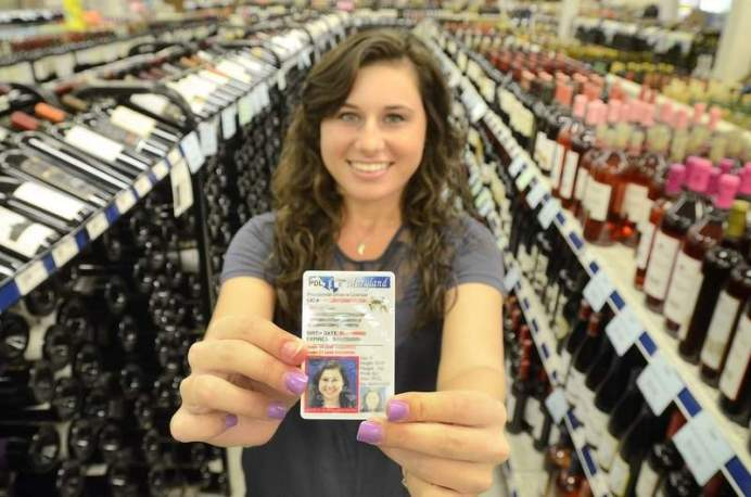 Rachel is an underage volunteer for the Montgomery County Liquor Board. She poses in a Montgomery County liquor and wine store with her Maryland underage driver's license, which is vertical and has a red box around her picture to indicate that she is not old enough to purchase alcohol. The Gazette blurred the personal details on her license. Dan Gross/The Gazette
