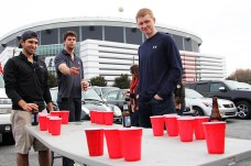 Auburn senior Drew Sansing (center) throws a ping pong ball during a game of beer pong in front of the Georgia Dome in Atlanta on Dec. 5. MIKE KREBS/THE MANEATER