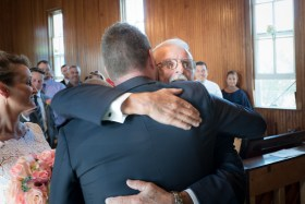 Groom hugging father of the bride at the Spray Beach Chapel in Beach Haven NJ