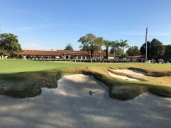 Bunkering in front of 9th green with clubhouse in background.