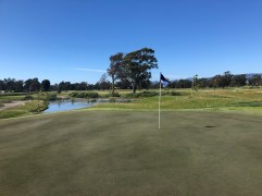 Close view of 7th green with water hazard behind.