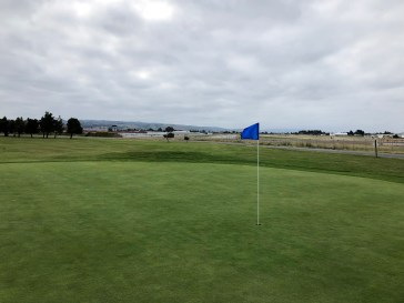 Behind 17th green with airport in the background.