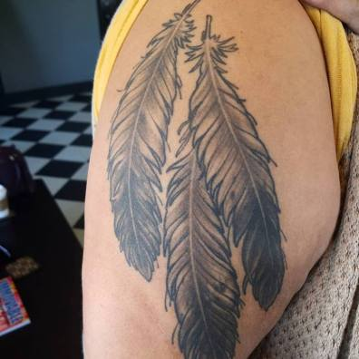 healed black and grey feather tattoo