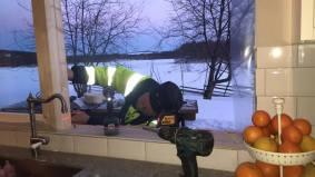 Tommy mäter in de nya fönstren ovanför diskbänken