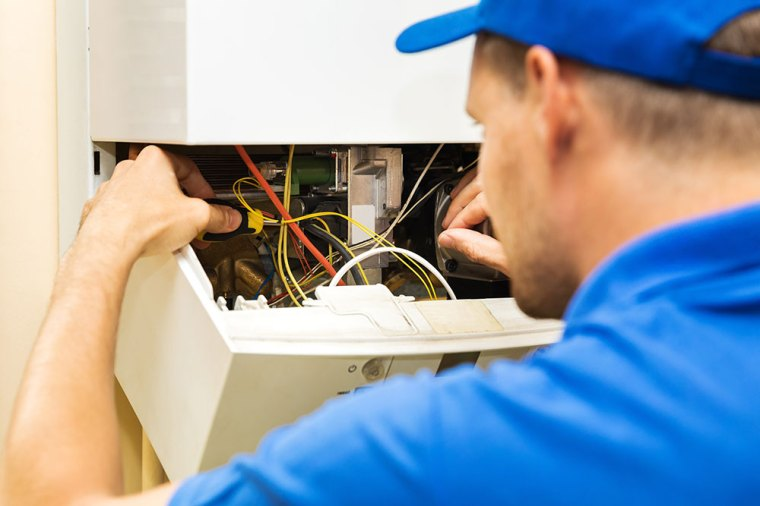 picture of an engineer repairing a boiler