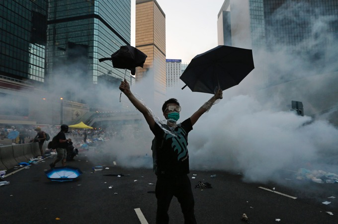A protester (C) raises his umbrellas in front of tear gas which was fired by riot police to disperse protesters blocking the main street to the financial Central district outside the government headquarters in Hong Kong, September 28, 2014. Hong Kong police used tear gas for the first time on Sunday to disperse pro-democracy protests and baton-charged the crowd blocking a key road in the government district after Hong Kong and Chinese officials warned against demonstrations. [REUTERS/Tyrone Siu]