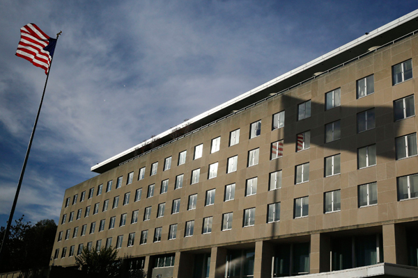 A U.S. national flag and its shadow on the Harry S. Truman Building at the Department of State are pictured in Washington, in this October 24, 2014 file photo. REUTERS/Larry Downing/Files