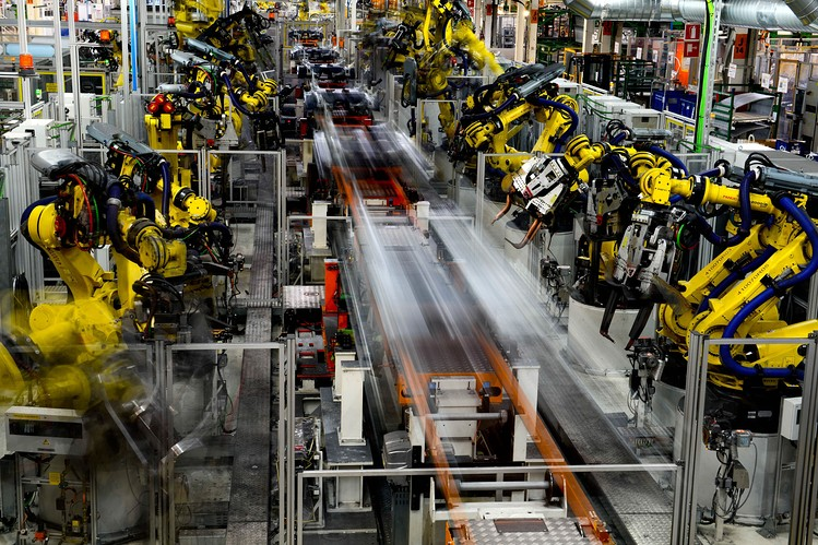Robots work on vehicles on the production line during assembly at Volkswagen AG's Seat automobile plant in Martorell, Spain. [Reuters]