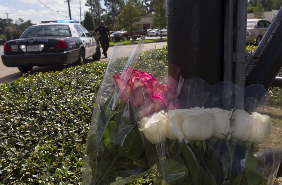 A police officer stands at the entrance to a movie theatre, near flowers left for victims of a Thursday night shooting, in the theatre in Lafayette, Louisiana July 24, 2015. John Russell Houser, an Alabama drifter, opened fire inside the crowded movie theater, killing two women, police said, in the latest act of random gun violence to shock the United States. REUTERS/Lee Celano.