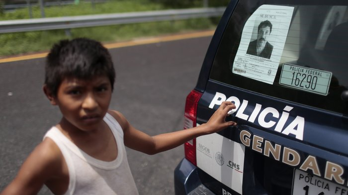 """A boy stands next to a police car with a picture of fugitive drug lord Joaquin """"El Chapo"""" Guzman's at a checkpoint on the highway connecting Mexico City and Acapulco, in Guerrero State, Mexico. Pedro Pardo, AFP/Getty via NPR"""