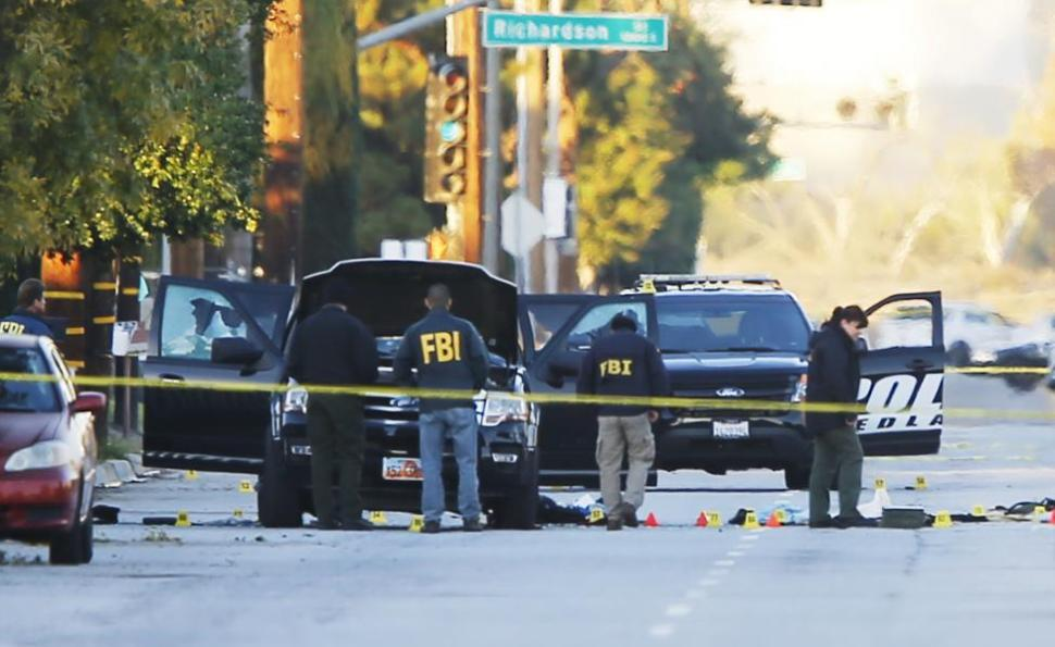 FBI and police are seen around a vehicle in which two suspects were shot following a mass shooting in San Bernardino.  REUTERS/Mike Blake