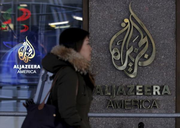 A woman passes by the Al Jazeera America broadcast center in NYC Jan. 13, 2016.  REUTERS