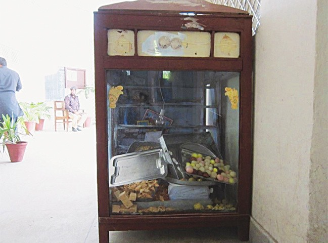 The display case at Tariq Hotel and Sweet Shop, from which the poisoned laddu were sold. Police seized the cabinet and its contents for analysis. [Dawn]