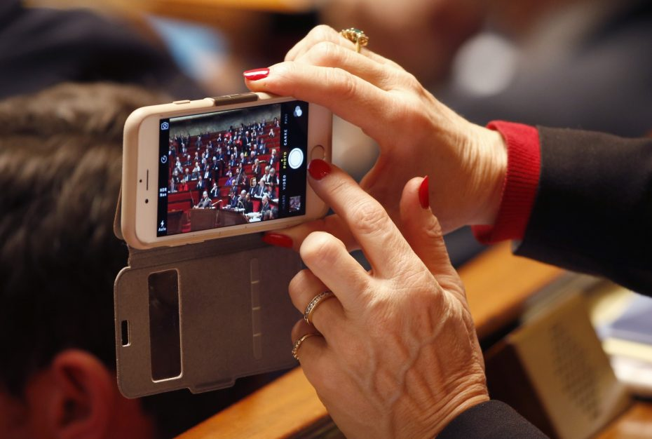 A deputy takes a picture with her mobile phone during a debate to extend a state of emergency, at the National Assembly in Paris, France, November 19, 2015 following the series of deadly attacks on last Friday in the French capital. REUTERS
