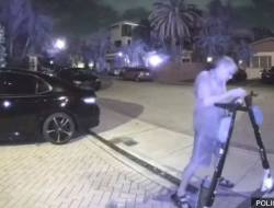 Screenshot of a security camera showing a man vandalizing escooters