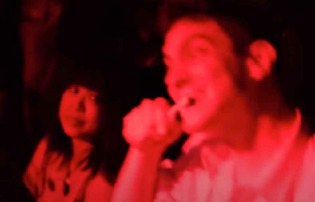 Fellow brushes his teeth during Japanese noise music concert by Merzbow