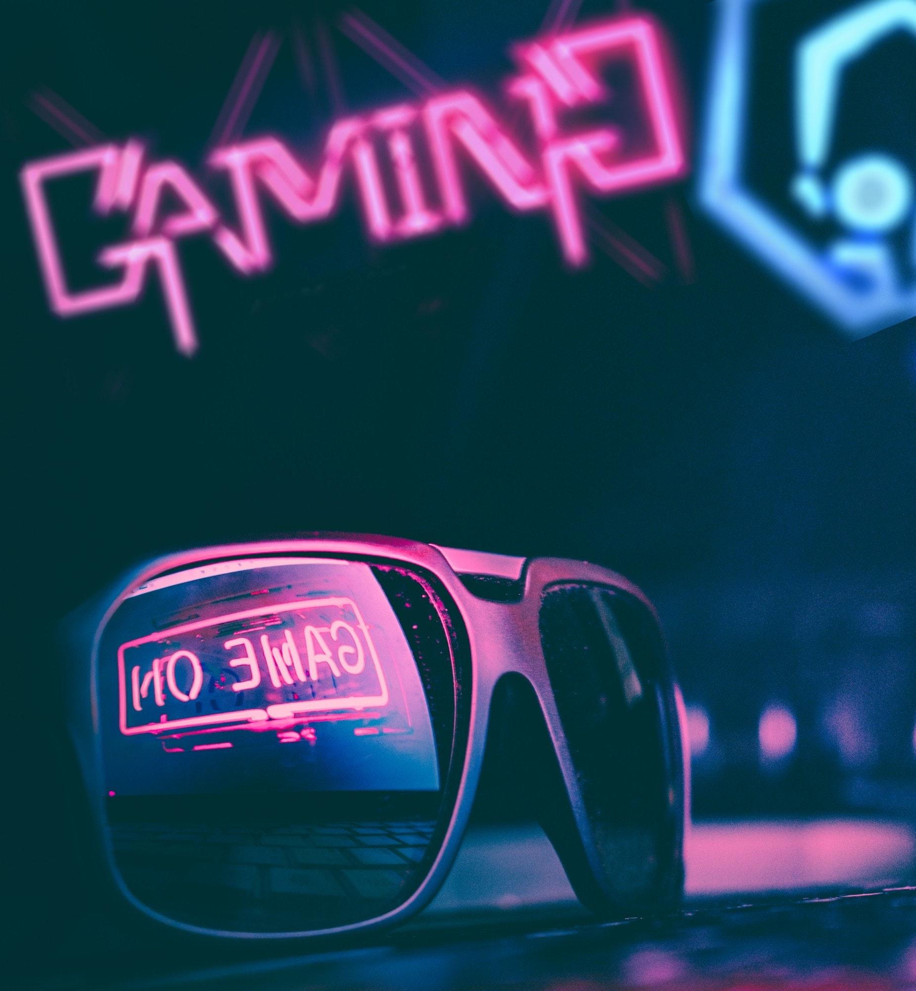 Trendy sunglasses reflecting neon light sign in dark room