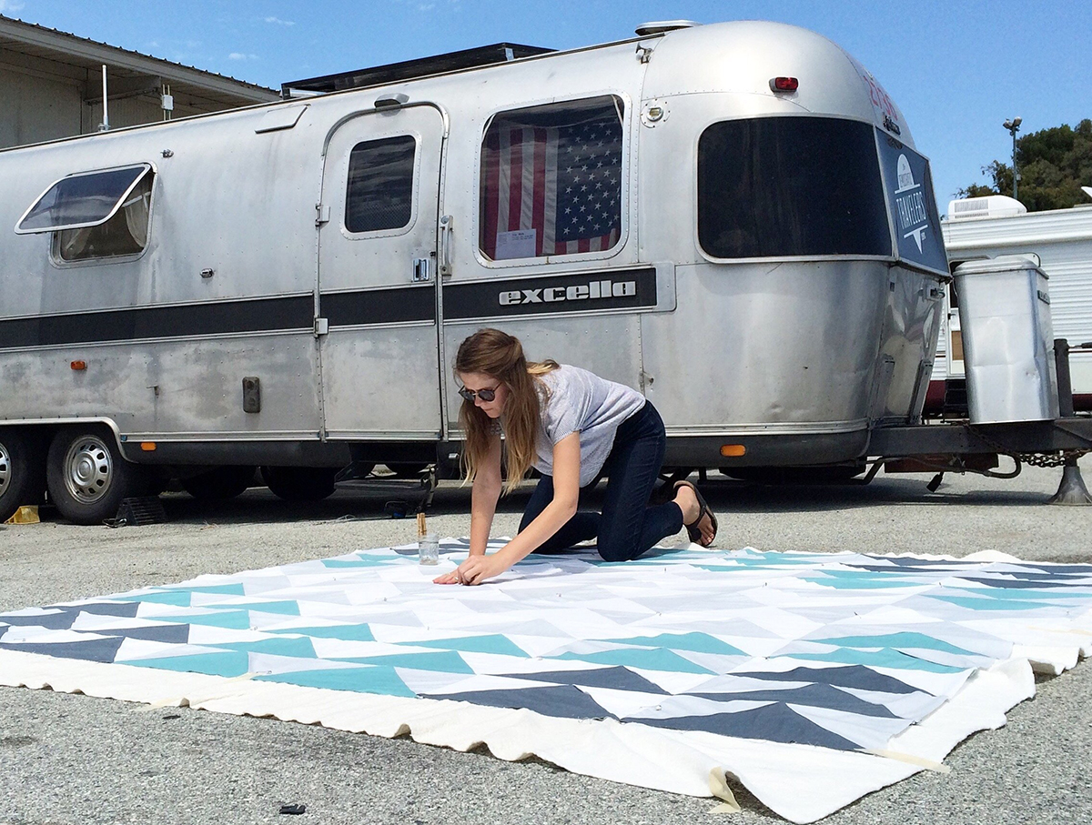 Laura Preston designing a quilt next to her Airstream trailer